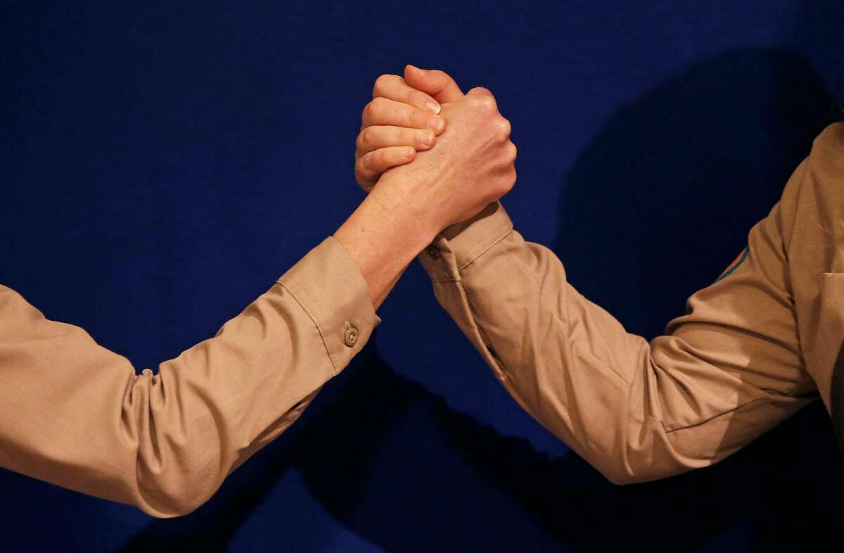 Alison Pebworth, left, and Hannah Ireland demonstrate different types of handshakes before opening the Unofficial Department of Handshakes on Friday, Jan. 12, 2018 at City Hall in San Francisco, Calif.