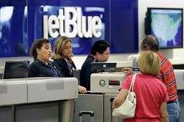 FILE - In this Wednesday, Oct. 26, 2016, file photo, JetBlue Airways ticket agents assist passengers at the ticket counter at Tampa International Airport in Tampa, Fla. Dozens of companies, including JetBlue, have announced they are giving their employees bonuses, following the passage of the Republican tax plan that President Donald Trump signed into law in December 2017. (AP Photo/Chris O'Meara, File)
