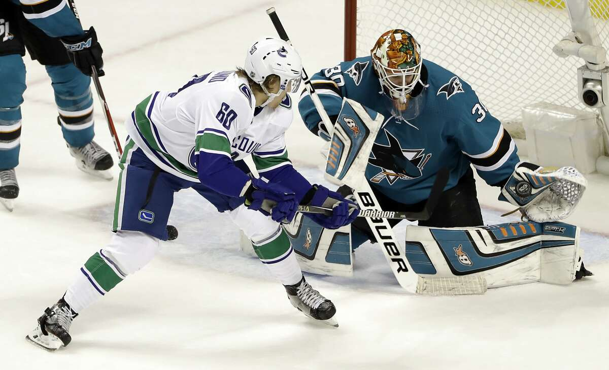 San Jose Sharks goalie Aaron Dell (30) stops a shot from Vancouver Canucks center Markus Granlund (60) during the overtime of an NHL hockey game Thursday, Dec. 21, 2017, in San Jose, Calif. San Jose won 5-4. (AP Photo/Marcio Jose Sanchez)