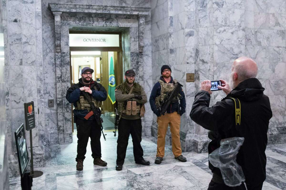 A group of young men pose for a photograph in front of Governor Inslee's office while open carrying during Rally 4 UR Rights, at the Washington State Capitol building on Friday, Jan. 12, 2018.