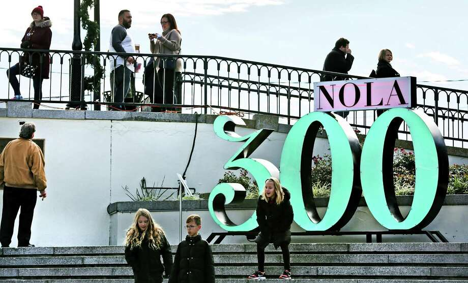 "Tourists and locals hang out near a ""NOLA 300"" sign at Washington Artillery Park as New Orleans celebrates it's Tricentennial, the same year that San Antonio does, on Friday, Jan. 5, 2018. Photo: Bob Owen, Staff / San Antonio Express-News / ©2017 San Antonio Express-News"