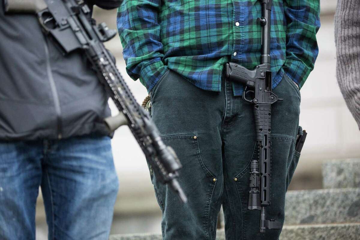 Gun rights advocates open carry to exercise their rights on the steps of the Washington State Capitol building on Friday, Jan. 12, 2018.