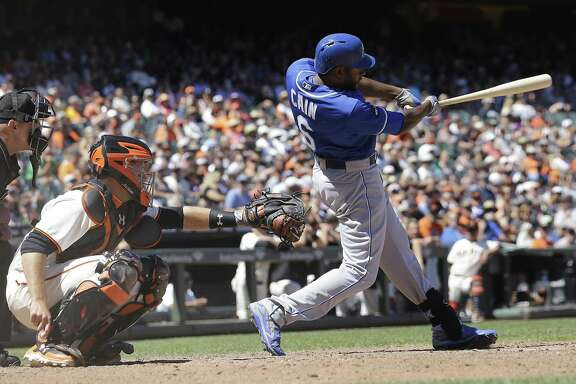 Kansas City Royals' Lorenzo Cain, right, hits an RBI-single in front of San Francisco Giants catcher Buster Posey during the eighth inning of a baseball game in San Francisco, Wednesday, June 14, 2017. The Royals won 7-2. (AP Photo/Jeff Chiu)