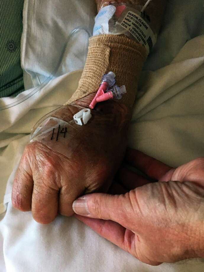 Hearst Connecticut Media reporter and columnist Ken Dixon holds his father's hand at Stamford Hospital. Claude Dixon, who died at 92 on Jan. 7, 2018, served in the U.S. Navy during World War II, taught in Stamford public schools and worked as a journalist for WSTC radio in Stamford and the Bridgeport Post and The Telegram. Photo: Contributed Photo / Stamford Advocate  contributed