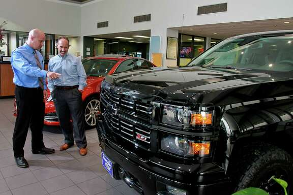 Awni Kawar, left, with Munday Chevrolet at 17800 North Fwy., showing a 2015 Silverado 1500 Z71 4WD LTZ Crew Cab truck to customer Randy Parker. Munday Chevrolet was purchased last year by Group 1 Automotive. (For the Chronicle/Gary Fountain, May 28, 2015)