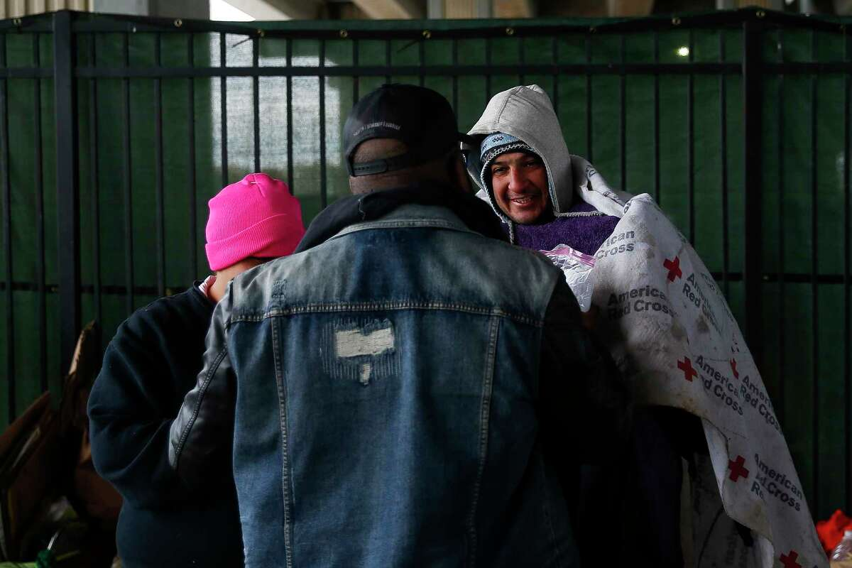 Star of Hope outreach case manager Kenneth DeVon, center, passes out blankets to the homeless as temperatures hover in the 30s on Jan. 2, 2018 in Houston. ( Michael Ciaglo / Houston Chronicle)