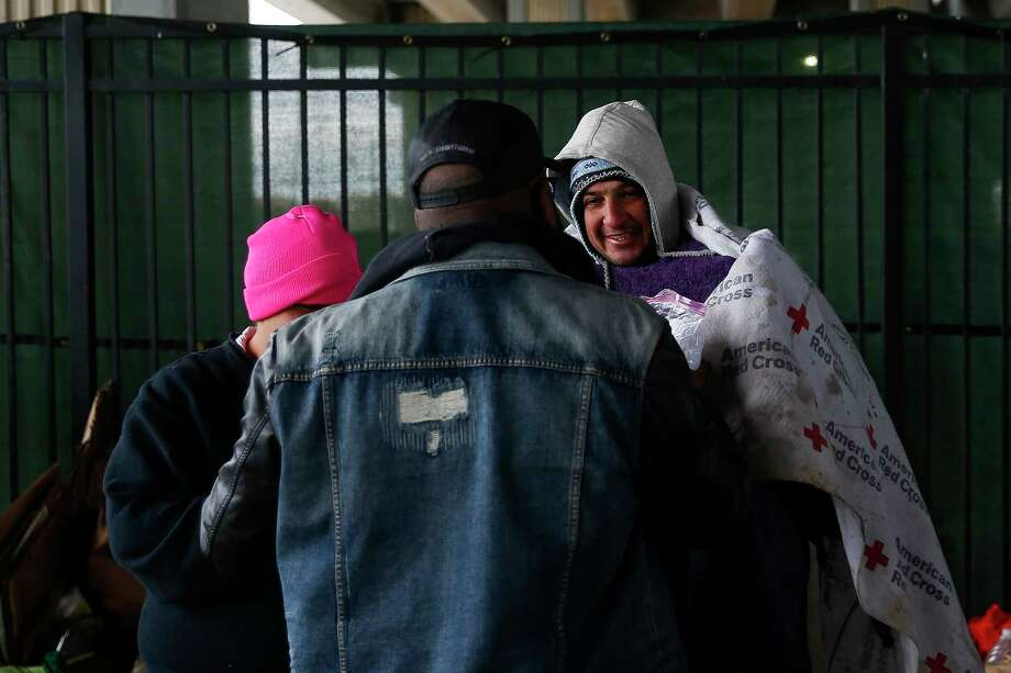 Star of Hope outreach case manager Kenneth DeVon, center, passes out blankets to the homeless as temperatures hover in the 30s on Jan. 2, 2018 in Houston. ( Michael Ciaglo / Houston Chronicle) Photo: Michael Ciaglo, Houston Chronicle / Michael Ciaglo