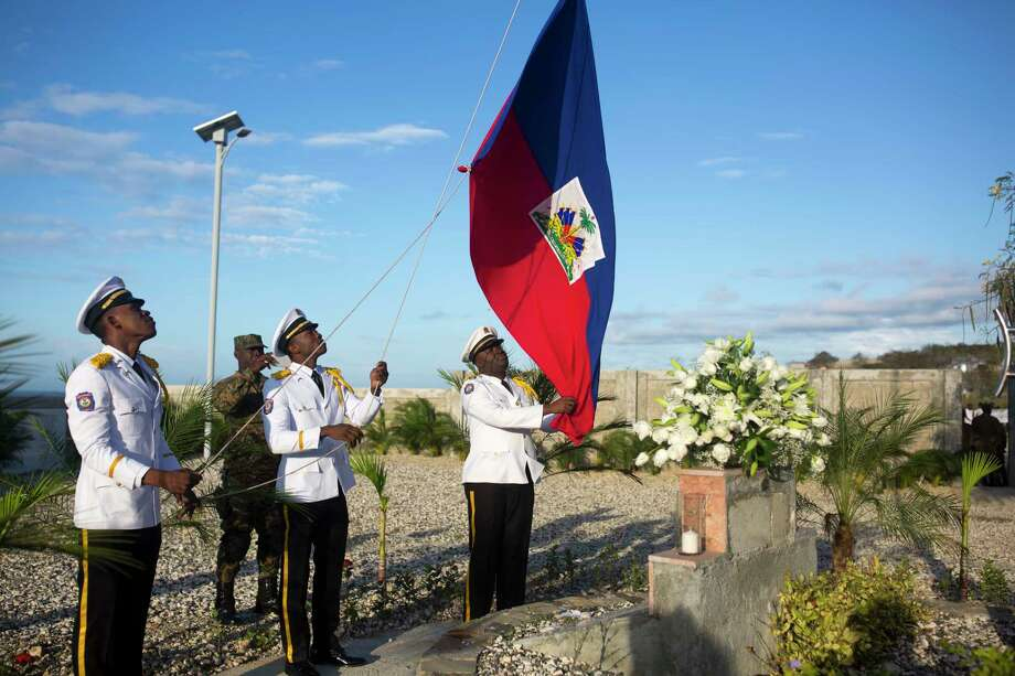 National police officers raise a Haitian national flag during a memorial service honoring the victims of the 2010 earthquake, at Titanyen, a mass burial site north of Port-au-Prince, Haiti, Friday, Jan. 12, 2018. Haitians reacted with outrage Friday to reports that President Donald Trump used a vulgar remark to describe the country on the eve of the anniversary of the 2010 earthquake, one of the deadliest disasters in modern history. (AP Photo/Dieu Nalio Chery) Photo: Dieu Nalio Chery, STR / Copyright 2018 The Associated Press. All rights reserved.
