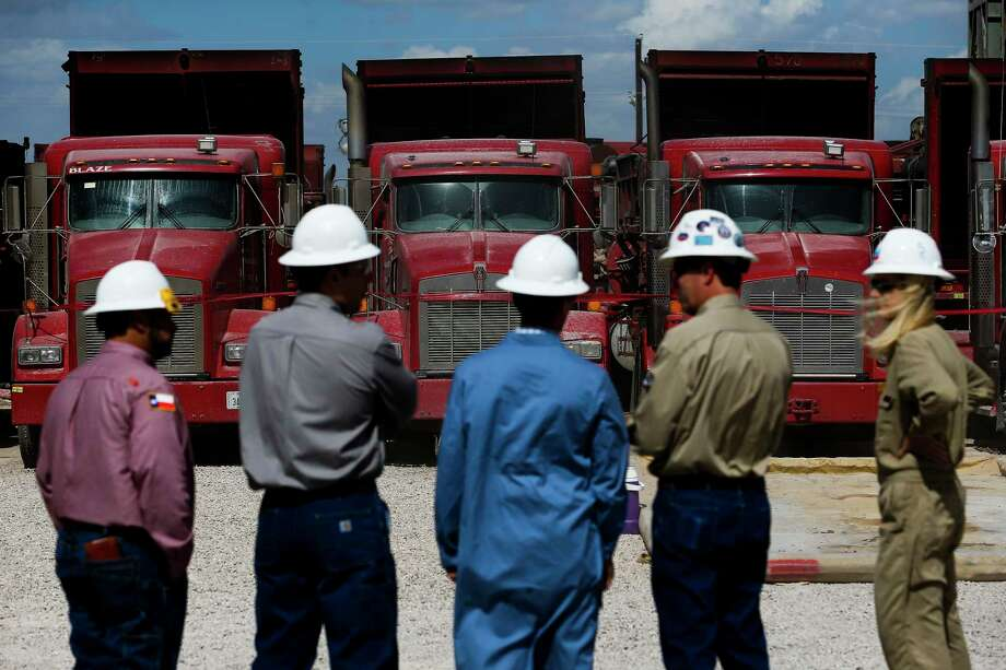 People stand in front of trucks at a Chevron hydraulic fracturing site Wednesday, July 19, 2017 in Midland. ( Michael Ciaglo / Houston Chronicle ) Photo: Michael Ciaglo, Staff / Michael Ciaglo