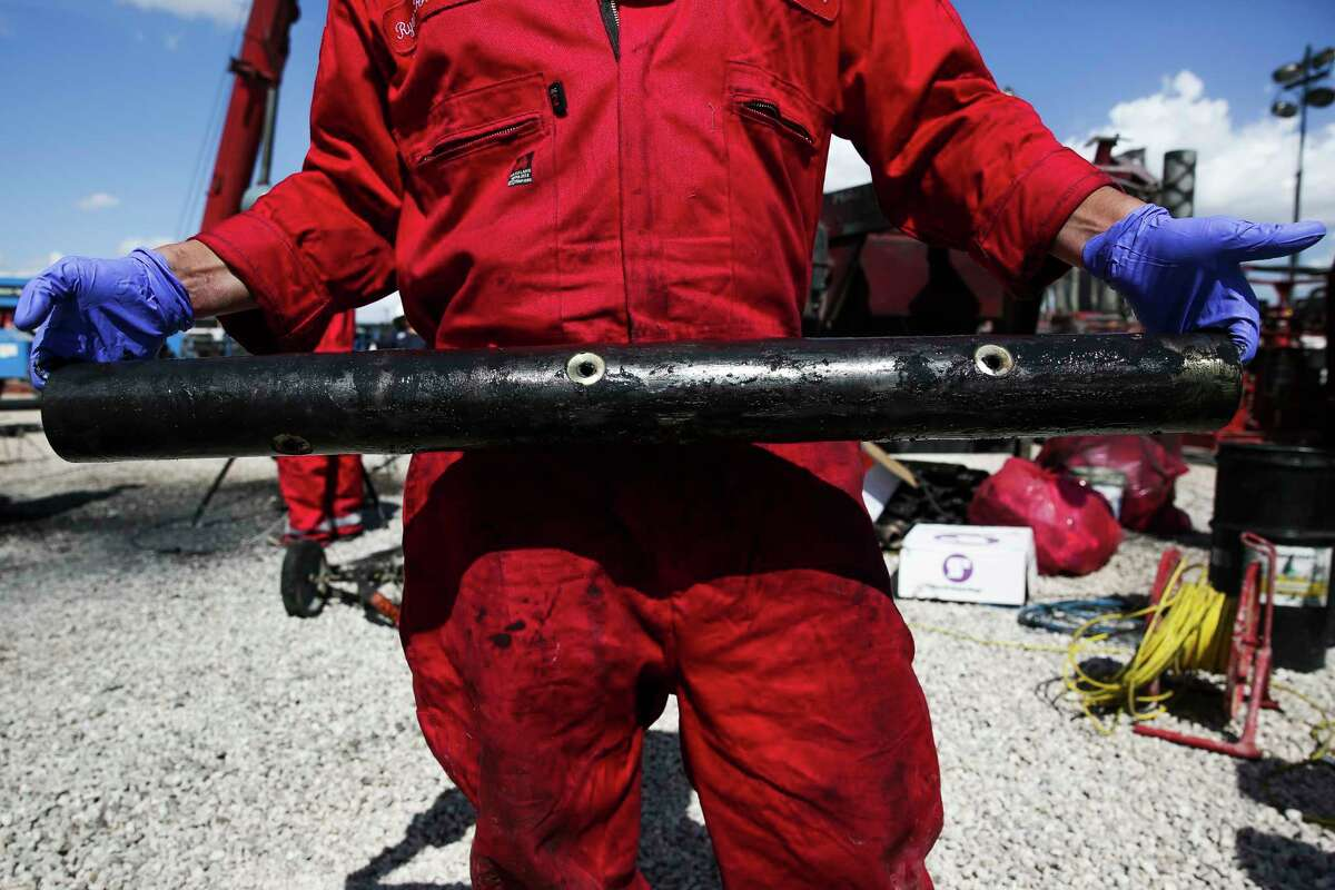 A worker holds a used charge sleeve after hydraulic fracturing operations at Chevron drilling site Wednesday, July 19, 2017 in Midland. ( Michael Ciaglo / Houston Chronicle )