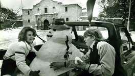Snow and a snowman in front of the Alamo Jan. 12, 1985. Lolly Flowers (left) and Leslie Roberts built the snowman in the back of a friend's truck parked by the Alamo.