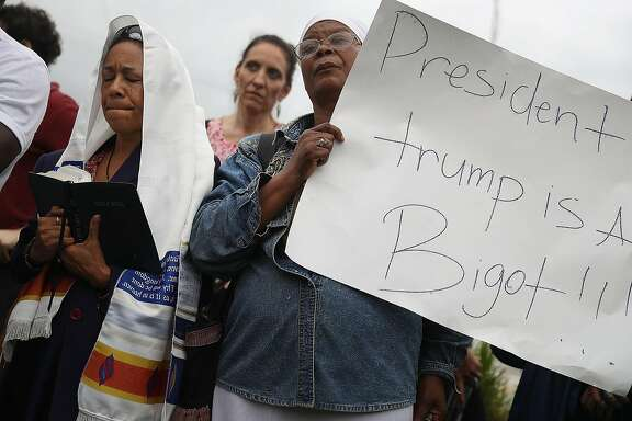 MIAMI, FL - JANUARY 12: (EDITORS NOTE: Caption contains profanity.)  Minister Lorna Shuford and Pastor Marie Belizaire (L-R) join with others to mark the 8th anniversary of the massive earthquake in Haiti and to condemn President Donald Trump's reported statement about immigrants from Haiti, Africa and El Salvador on January 12, 2018 in Miami, Florida. President Trump is reported to have called those places 'shithole countries' whose inhabitants are not desirable for U.S. immigration.  (Photo by Joe Raedle/Getty Images)