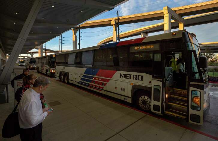 Morning commuters wait in line to board a Metro bus at the Grand Parkway Park and Ride on Dec. 20.