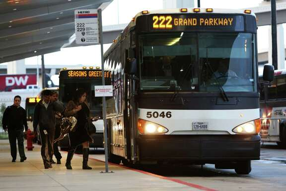 Morning commuters board a Metro bus at the Grand Parkway Park and Ride on Dec. 20.