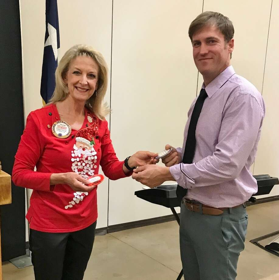 Recently Conroe Noon Lions Club member Adam Peterson (r) had earned enough points to exchange his red new member badge for his permanent blue name badge, presented by club President Helen Thornton (l) Photo: Submitted