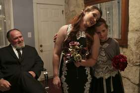 Morgan leans on her niece Amanda Pomeroy, 9, while Morgan's father, Darrell Harris, waits for the wedding to begin  on Thursday.