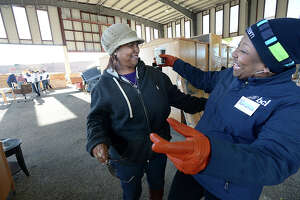 Deborah Welch gets a greeting from an old friend and volunteer Andrea Allen during the furniture distribution for Harvey-impacted families at the Pavilion in Port Arthur Friday.  Welch lost her Del Vista neighborhood home and furniture in Harvey's flooding. Various organizations, including Business and Community Lenders of Texas, Neighbor Works, and Operation Blessing worked together under the coordination of Port Arthur native Billy Filer, to gather furniture donations from several Las Vegas hotels. The pieces were distributed to 112 Port Artur families who lost their homes and belongings in last year's flood. Photo taken Friday, January 12, 2018 Kim Brent/The Enterprise