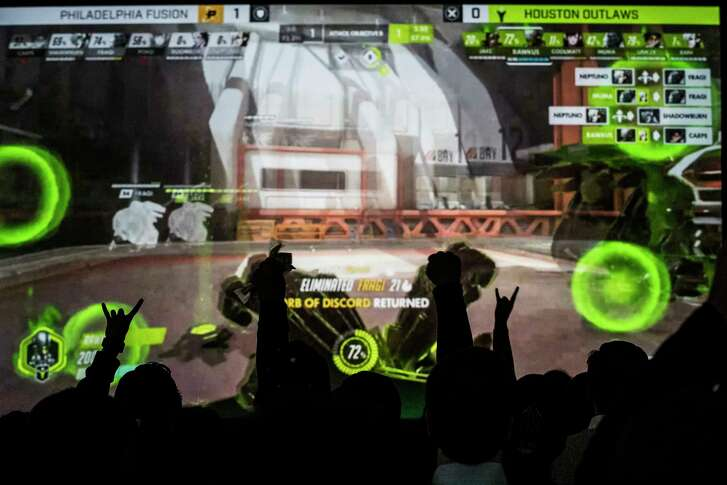 Houston Outlaws fans cheer during a watch party for the esports team Thursday night at a warehouse that will be converted into a $70 million 120,000-square-foot co-working space.