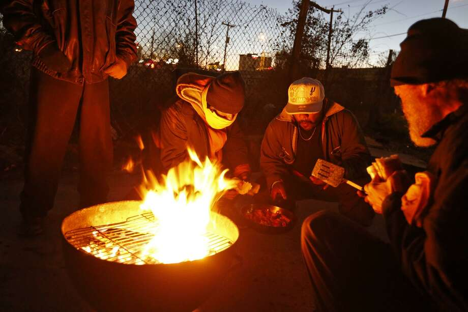 Robert Diaz (center left), Junior Rodriguez (center right) and other homeless men try to stay warm Thursday while cooking bacon and chicken near the Hays Street Bridge. Photo: Edward A. Ornelas /San Antonio Express-News / © 2018 San Antonio Express-News