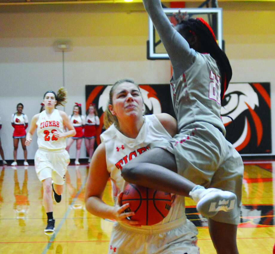Edwardsville senior forward Rachel Pranger, left, is fouled as she goes up for a shot during Friday's Southwestern Conference game against Alton.