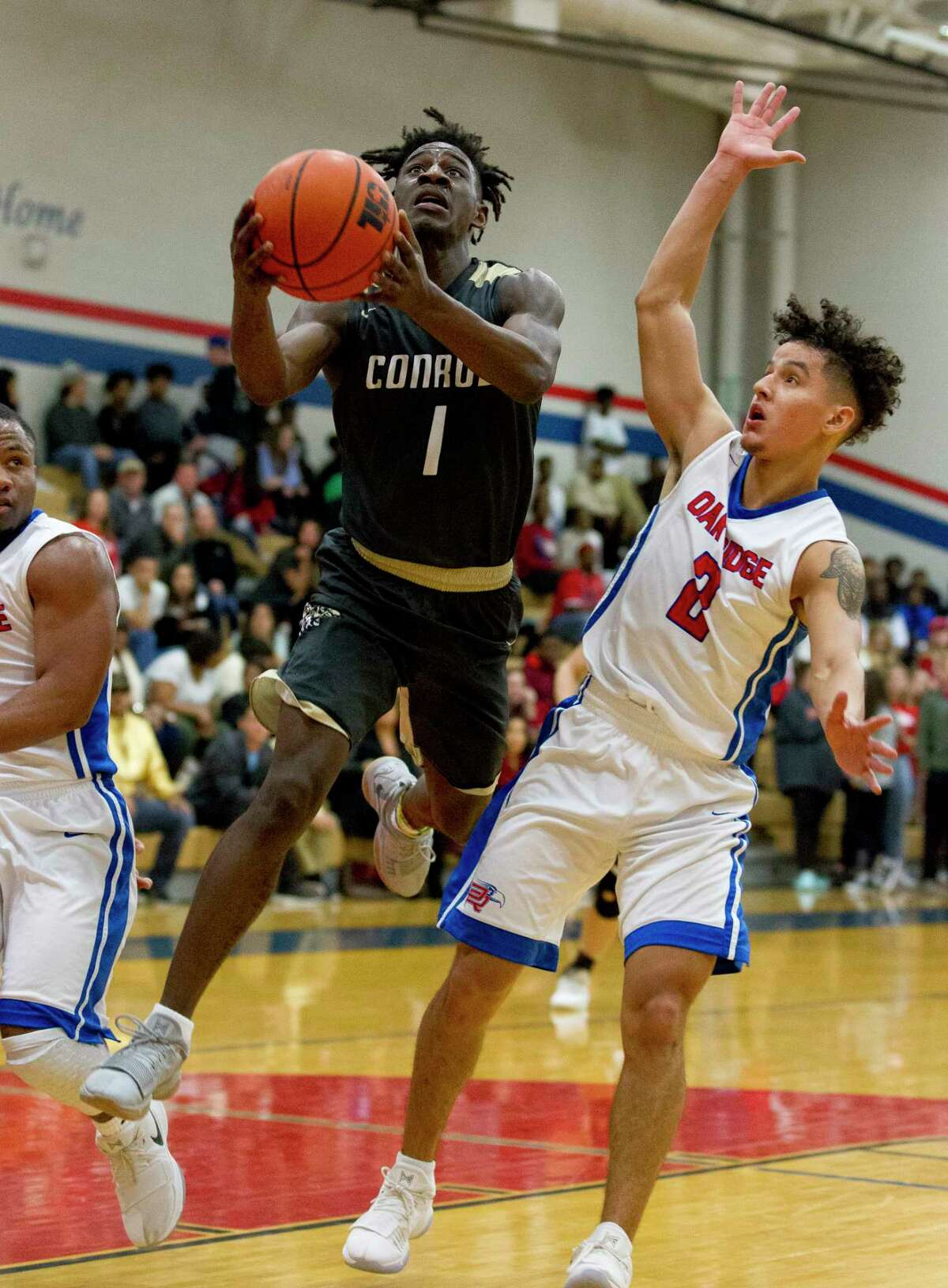 Conroe guard Jay Lewis (1) shoots under pressure by Oak Ridge guard Cristian Calix (2) during the fourth quarter of a District 12-6A high school boys basketball game at Oak Ridge High School, Friday, Jan. 12, 2018.