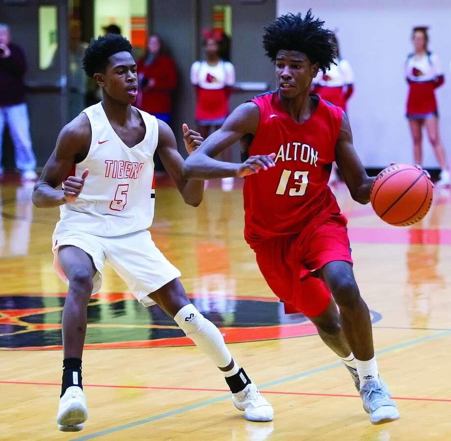 Edwardsville's Lavontas Hairston (5) defends Alton's Malik Smith (13) during Friday's Southwestern Conference game against Alton inside Lucco-Jackson Gymnasium. Photo: Scott Kane, For The Intelligencer