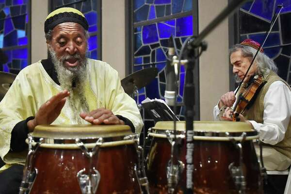 Alvin Abu Carter plays the congos with violinist Stacy Phillips, members of the Afro-Semitic Experience, at the annual interfaith service in tribute to the Rev. Martin Luther King Jr. at Congregation Mishkan Israel in Hamden Friday.