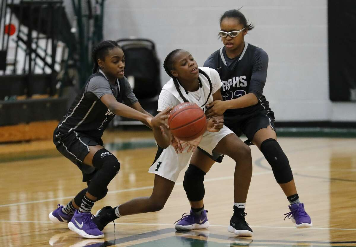 Ridge Point Panthers Raven Adams (10) and Aleighyah Fontenot (33) battle Fort Bend Hightower Hurricanes Taelor Purvis (5) for the ball in the first half during the girls high school basketball game between the Ridge Point Panthers and the Fort Bend Hightower Hurricanes at Hightower High School in Missouri City, TX on Friday, January 12, 2018.