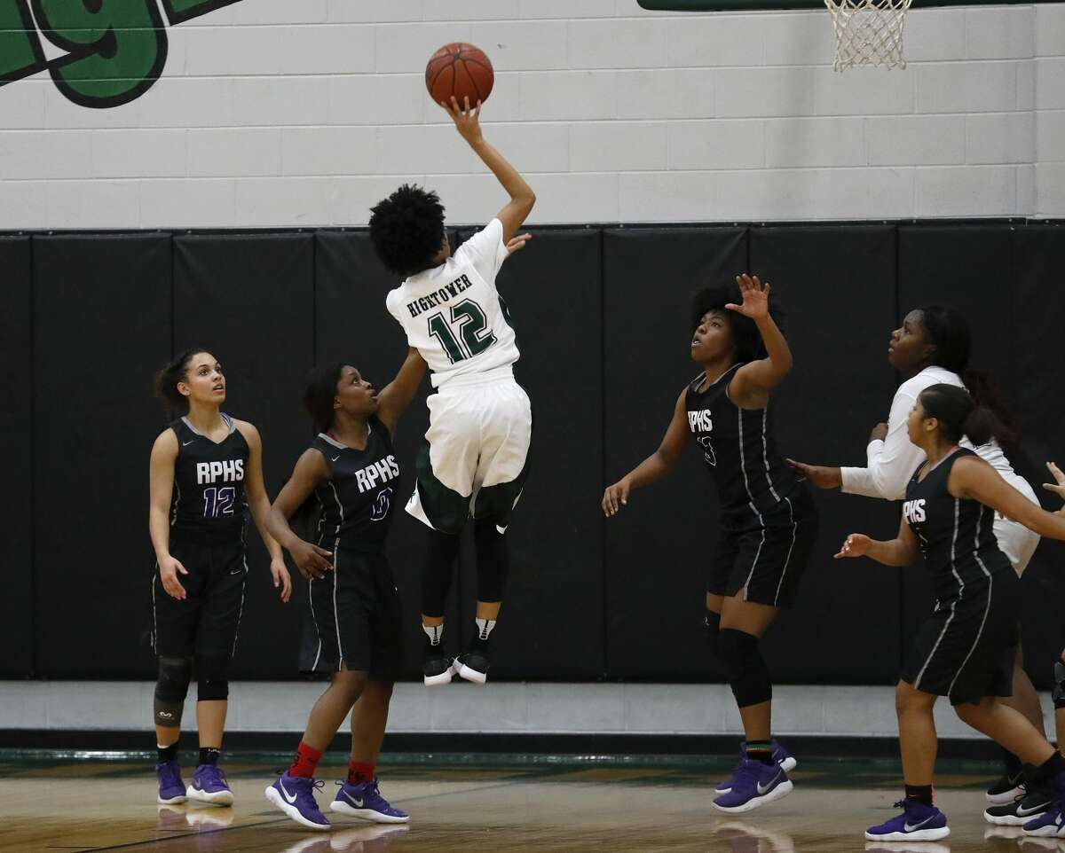 Fort Bend Hightower Hurricanes Sydni Johnson (12) shoots the ball defended by Ridge Point Panthers Alex Williams (13) and Jada McHenry (C) (0) in the first half during the girls high school basketball game between the Ridge Point Panthers and the Fort Bend Hightower Hurricanes at Hightower High School in Missouri City, TX on Friday, January 12, 2018.