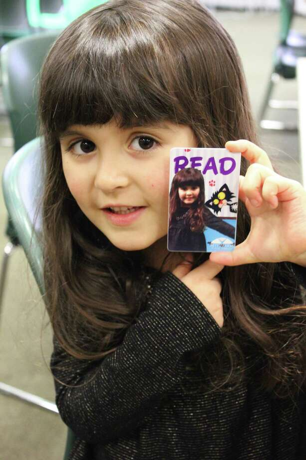 A young patron of the Bethlehem Public Library shows a personalized library card at a Jan. 9 program that used a green screen to superimpose their images onto a READ poster background that was printed onto a new card on the spot. (Photo by Kristen Roberts)