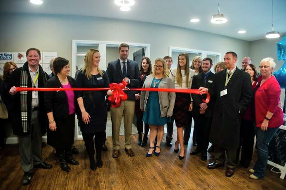 Staff of Bricks Real Estate Experts, along with Chamber of Commerce ambassadors, pose for a photo during a ribbon cutting ceremony at Bricks Real Estate Experts on Friday. (Katy Kildee/kkildee@mdn.net)