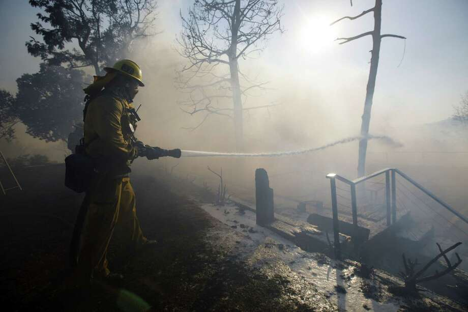 A firefighter hoses down a home's deck during the Skirball Fire in the Bel Air neighborhood of Los Angeles on Dec. 6, 2017. Photo: Bloomberg Photo By Patrick T. Fallon. / © 2017 Bloomberg Finance LP