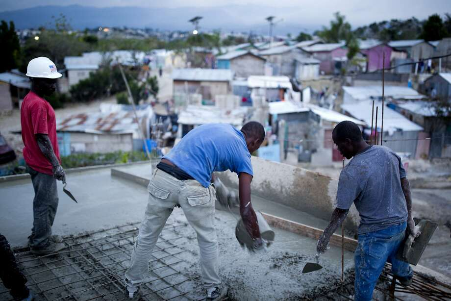 In this Saturday, Jan. 6, 2018 photo, construction workers build a concrete roof in the Caradeux refugee camp set up nearly eight years ago for people displaced by the 2010 earthquake, in Port-au-Prince, Haiti. Meant to be a temporary home the camp has morphed into a crowded shantytown where living in a concrete homes is seen as a return to normalcy. However the $7,000 price tag is out of reach for most of the displaced where half the Haitian population survives on less than $2 a day. (AP Photo/Dieu Nalio Chery) Photo: Dieu Nalio Chery, Associated Press