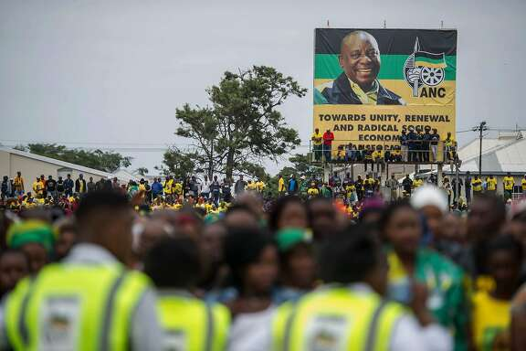 "Supporters stand under a banner bearing a portrait of African National Congress (ANC) President Cyril Ramaphosa during the ANC's 106th anniversary celebration at Absa Stadium in East London on January 13, 2018. The new head of South Africa's ruling ANC, Cyril Ramaphosa, pledged on January 13, 2018 to ""restore the credibility"" of the party after a spate of graft scandals involving President Jacob Zuma. / AFP PHOTO / MUJAHID SAFODIENMUJAHID SAFODIEN/AFP/Getty Images"