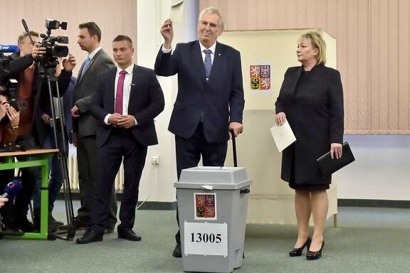 Presidential candidate and Czech President Milos Zeman shows his vote as his wife Ivana, right, looks on during the presidential election's first round vote in Prague, on Friday, Jan. 12, 2018. Czech Republic's president Milos Zeman and former president of the Czech Academy of Sciences Jiri Drahos are considered as favorites to advance to the runoffs on Jan. 26th and 27th.  (Vit Simanek/CTK via AP)