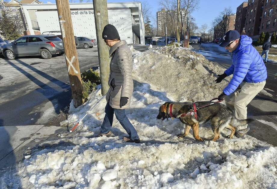 Honorato Kazmierczak and Phillip Magalnick, both of Stamford and legally blind, negotiate an ice covered walkway on Morgan Street in Stamford, Conn. on Wednesday, Jan. 10, 2018. Often times, the couple have difficulties with obstructions, such as snow and ice not being cleared from public right of ways following a snowstorm or motorists not yielding to pedestrians in a sidewalk, especially to a blind person. Photo: Matthew Brown / Hearst Connecticut Media / Stamford Advocate