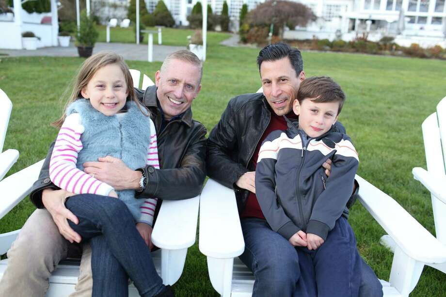 Chris Buckley and Mark Ciano pose for a family portrait with their twin children, Ayla and Connor Ciano-Buckley. Photo: Contributed Photo / Vicky Lavergne