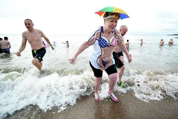 Sandy Kline (right) of New Haven emerges from the water during the 18th annual Icy Plunge for the Cure to benefit the West Haven Breast Cancer Awareness Program at Savin Rock Beach in West Haven on January 13, 2018.