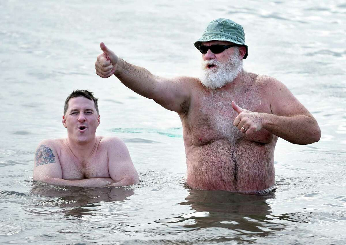 Christopher Molyneux (left) of Seymour and his father, Harry, of West Haven wade in the Long Island Sound during the 18th annual Icy Plunge for the Cure to benefit the West Haven Breast Cancer Awareness Program at Savin Rock Beach in West Haven on January 13, 2018. Molyneux' s mother is a survivor of breast cancer.