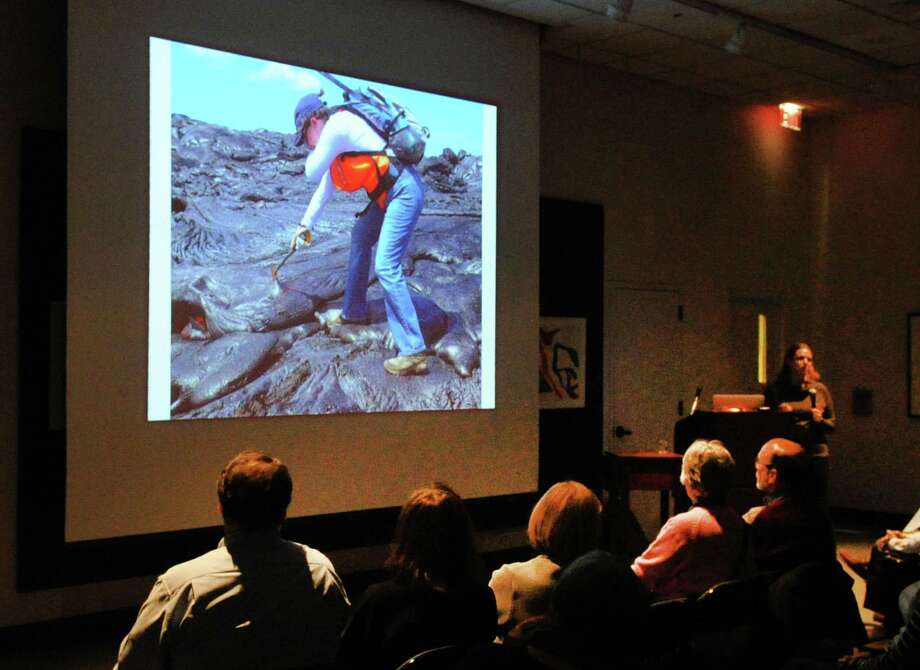 Dr. Einat Lev, assistant research professor at the Seismology, Geodynamics and Tectonics (SGT) group at Lamont-Doherty Earth Observatory of Columbia University, used a photo of herself at work studying lava during a speech she gave about the use of cutting-edge remote sensing technology to study lava at the Bruce Museum in Greenwich, Conn., Tuesday night, Jan. 9, 2018. Photo: Bob Luckey Jr. / Hearst Connecticut Media / Greenwich Time