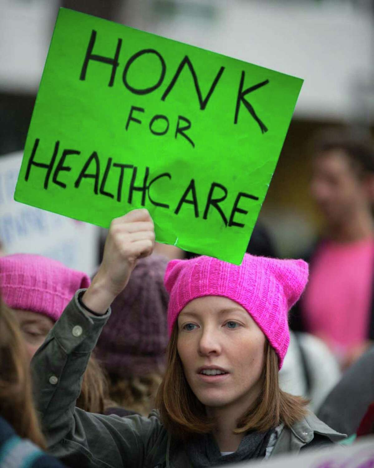 A women's rights supporter holds a sign up to traffic to counter protesters of the Capitol Hill Planned Parenthood on Saturday, Jan. 13, 2018.