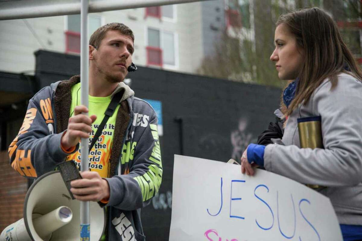 A anti-abortion and pro-choice demonstrator talk about religion during counterprotests outside Planned Parenthood.