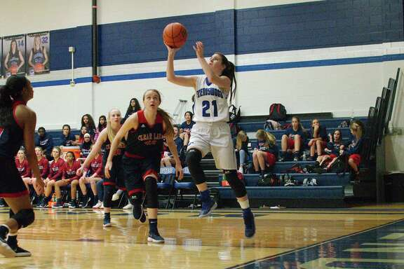 Friendswood's Kinsey Cole (21) drives to the basket past Clear Lake's Tara Kessner (42) Friday at Friendswood High School.
