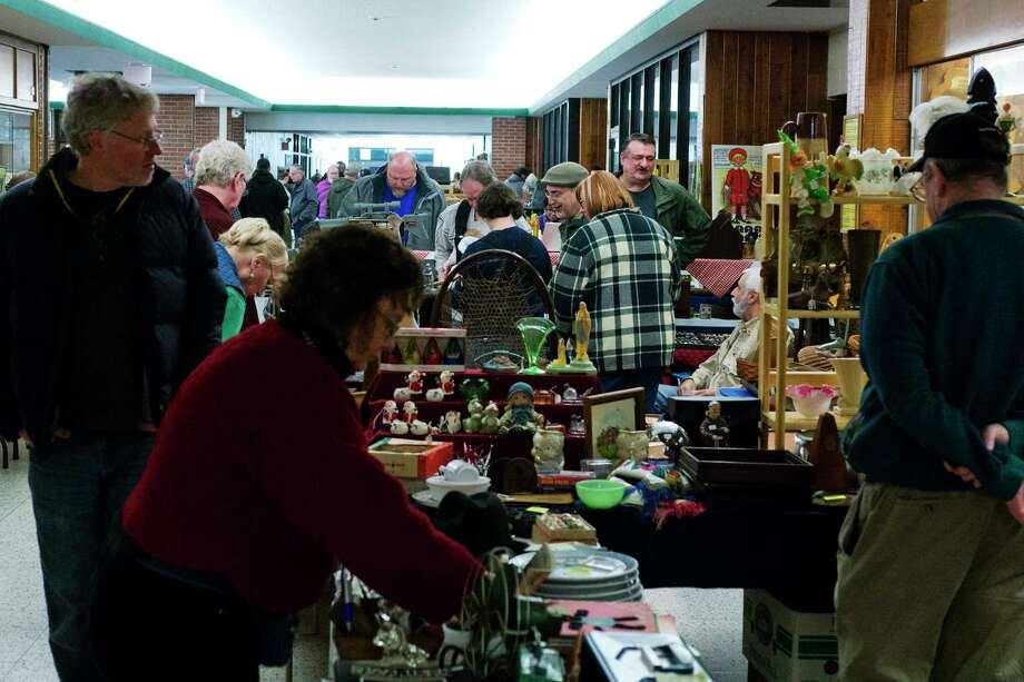 Shoppers look over items at various tables at the The Southern Saratoga County Woman's Club 40th Annual Antique Show and Sale on Sunday, Feb. 7, 2016, at Shenendehowa High School in Clifton Park, N.Y.  The yearly event is the groups largest fundraiser.  Money raised from the event helps the woman's club fund their Early Childhood Literacy program with over 500 books distributed so far to children up to eight years old.  The club also supports St. Ann Institute, Captain Youth and Family Services, the Ronald McDonald House and the group provides cash awards for art, crafts and writing contests for high school students.  (Paul Buckowski / Times Union) Photo: PAUL BUCKOWSKI / 10035312A