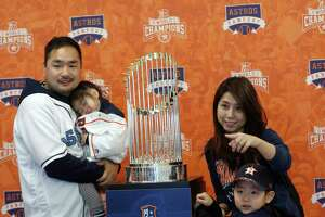 The Nakamura family gets their photo taken with the Astros Championship trophy during the Astros Fan Fest at. inute Maid Park,  Saturday, Jan. 13, 2018, in Houston.
