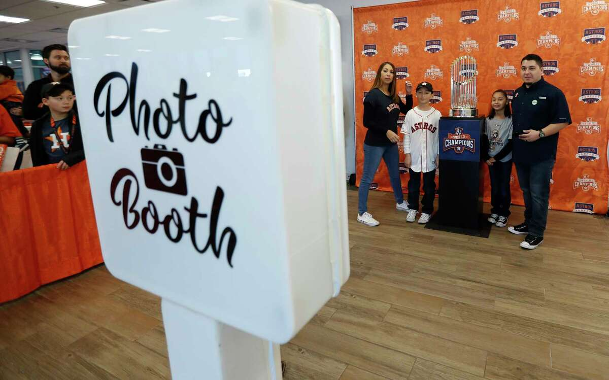 Fans get their photos taken with the Astros Championship trophy during the Astros Fan Fest at. inute Maid Park, Saturday, Jan. 13, 2018, in Houston.