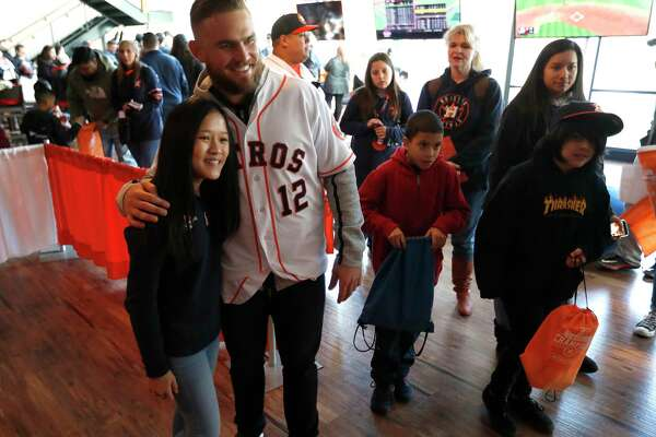 Astros catcher Max Stassi takes a photo with Sky Pham after playing a game of giant Jenga against her, during the Astros Fan Fest at. inute Maid Park,  Saturday, Jan. 13, 2018, in Houston.