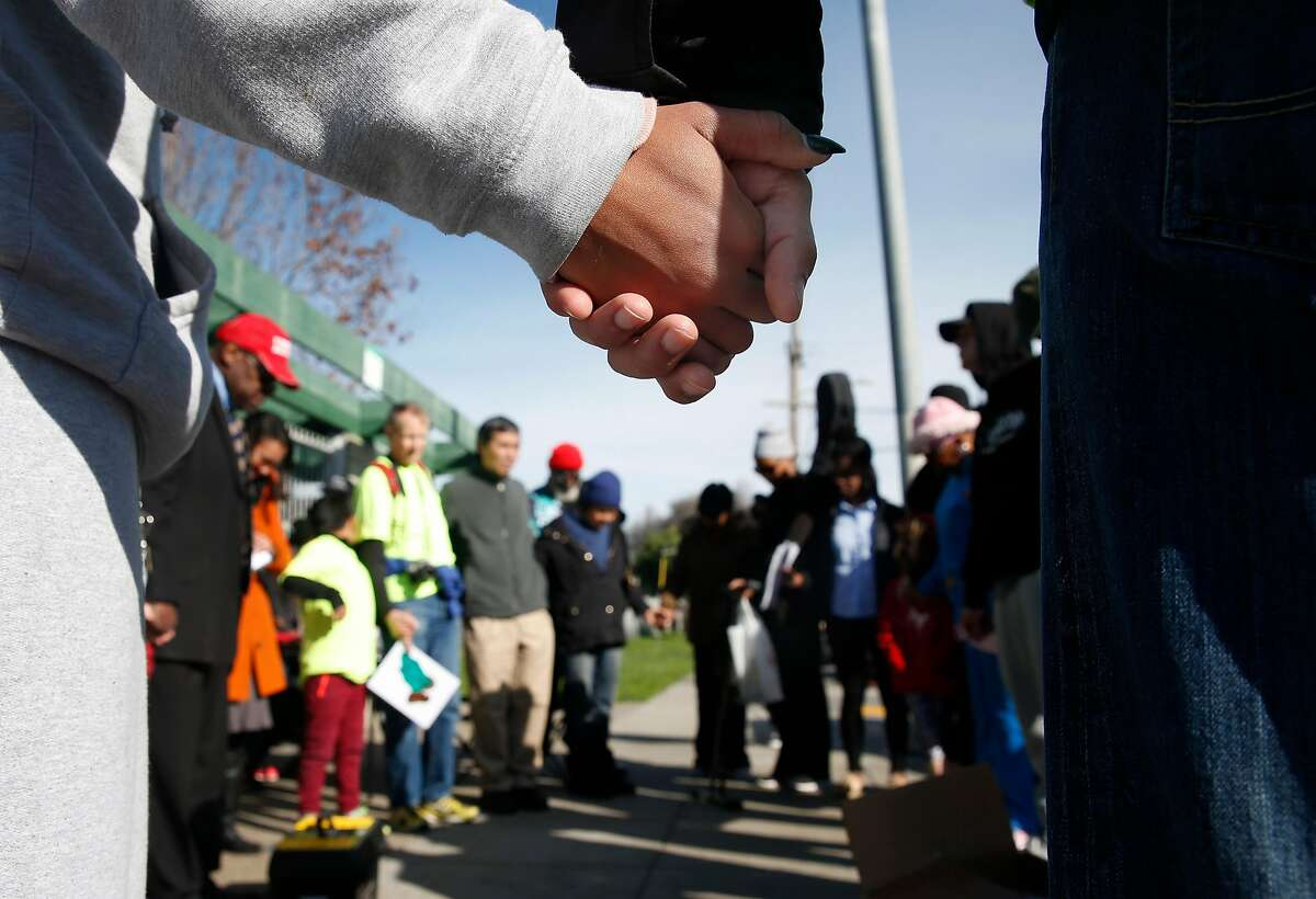Worshippers hold hands in a prayer circle at the conclusion of a march through the Bayview for the Martin Luther King Jr. birthday celebration in San Francisco, Calif. on Saturday, Jan. 13, 2018.