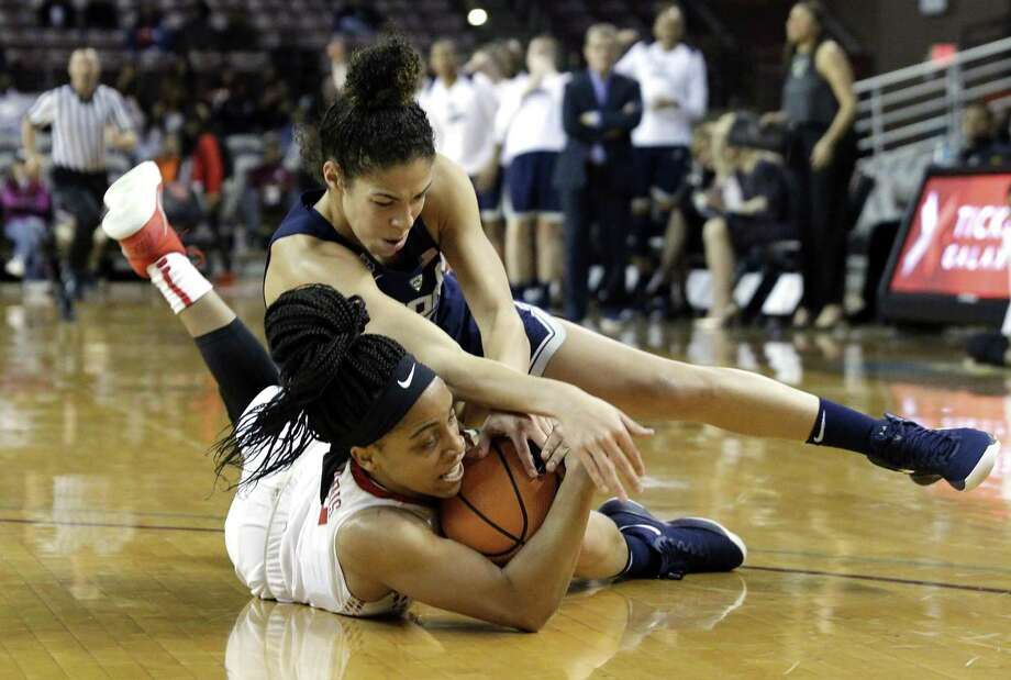 Houston's Angela Harris, left, fights for a loose ball with UConn's Crystal Dangerfield on Saturday. Photo: Michael Wyke / Associated Press / © Associated Press 2017