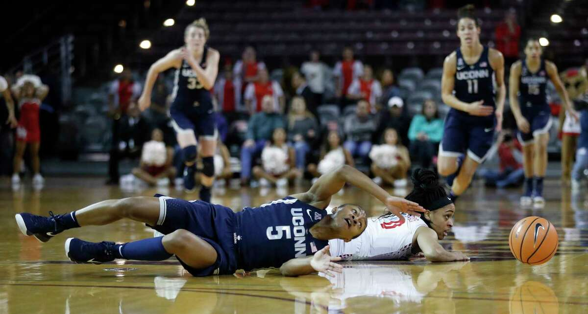 Connecticut Huskies guard Crystal Dangerfield (5) reaches for a loose ball after colliding with Houston Cougars guard Angela Harris during the first half of a NCAA basketball game at Texas Southern University Saturday, Jan. 13, 2018, in Houston.